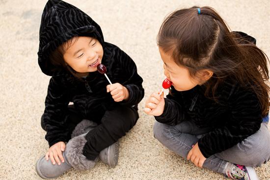 Girls in Cute Hoodies Enjoy Lollipops